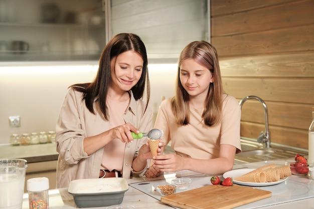 彼女の母親の隣の台所のテーブルのそばに立っているかなり金髪の10代の少女は、テーブルの上のワッフルコーンにおいしい自家製アイスクリームを入れています