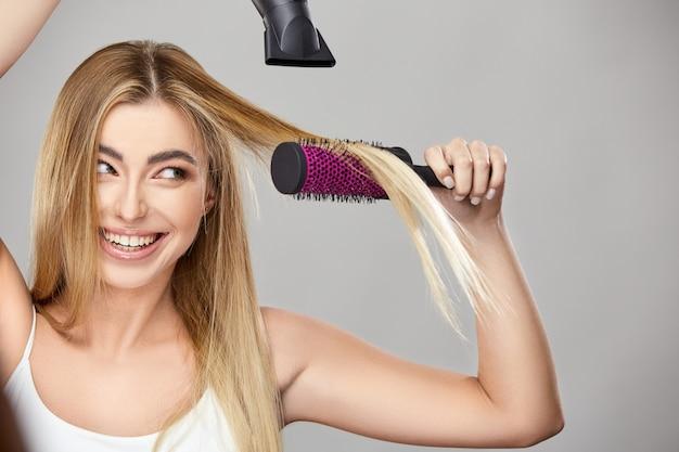 Довольно блондинка использует фен для своих здоровых длинных волос и улыбается, красивая девушка с феном, изолированные на серой стене