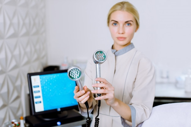 Pretty blond woman doctor cosmetolotgist and beautician holding a tool for mesotherapy led photon light therapy rf skin rejuvenation, standing in beauty salon or clinic.
