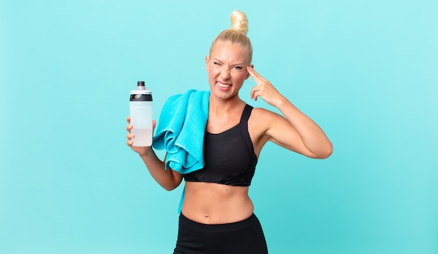 Pretty blond woman feeling confused and puzzled, showing you are insane. fitness concept