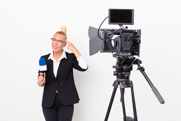 Pretty blond woman feeling confused and puzzled, showing you are insane and holding a pmicrophone. presenter concept