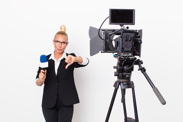 Довольно белокурая женщина чувствует крест, показывает палец вниз и держит микрофон. концепция ведущего