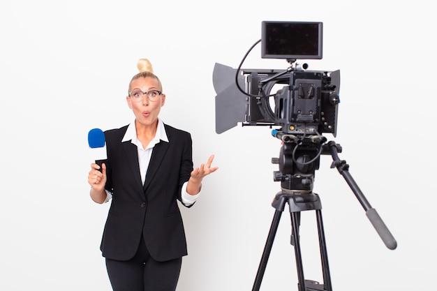 Довольно белокурая женщина, чувствуя себя чрезвычайно потрясенной и удивленной и держащей микрофон. концепция ведущего