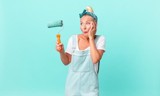Красивая блондинка женщина чувствует себя счастливой, взволнованной и удивленной и красит стену
