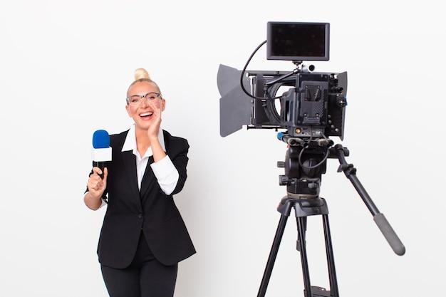 Довольно белокурая женщина чувствует себя счастливой, громко кричит, прижав руки ко рту и держа микрофон. концепция ведущего
