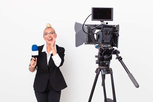 Pretty blond woman feeling happy,giving a big shout out with hands next to mouth and holding a pmicrophone. presenter concept