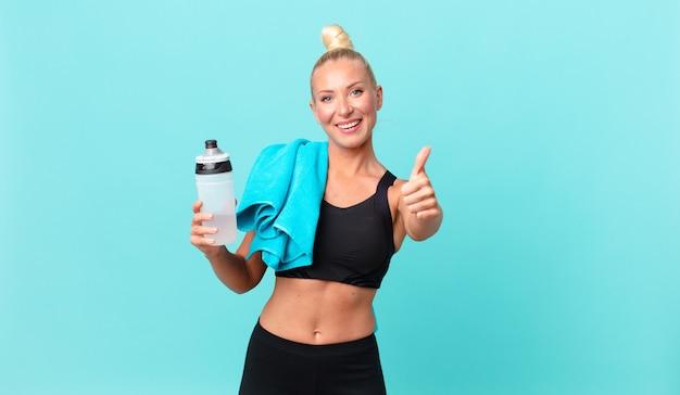 親指を立てて前向きに笑って、誇りを感じているかなり金髪の女性。フィットネスコンセプト Premium写真