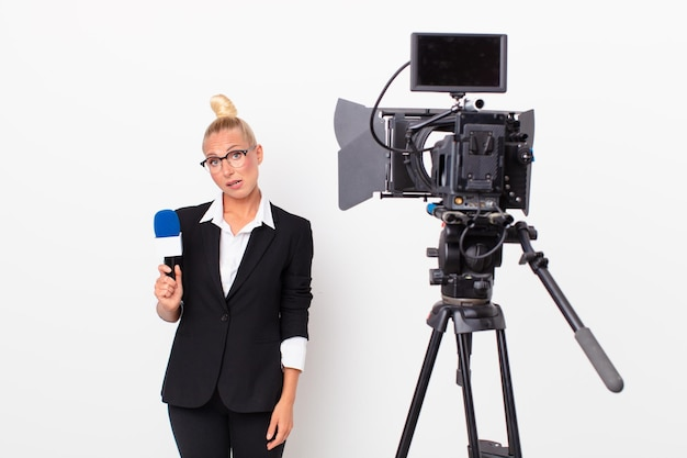 Pretty blond woman feeling puzzled and confused and holding a pmicrophone. presenter concept