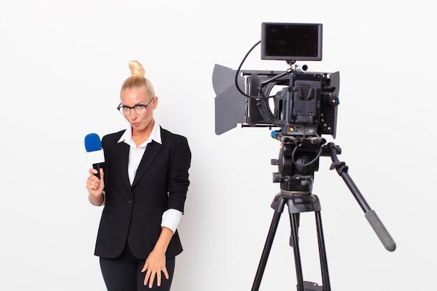 Довольно белокурая женщина грустит, расстроена или злится, смотрит в сторону и держит микрофон. концепция ведущего