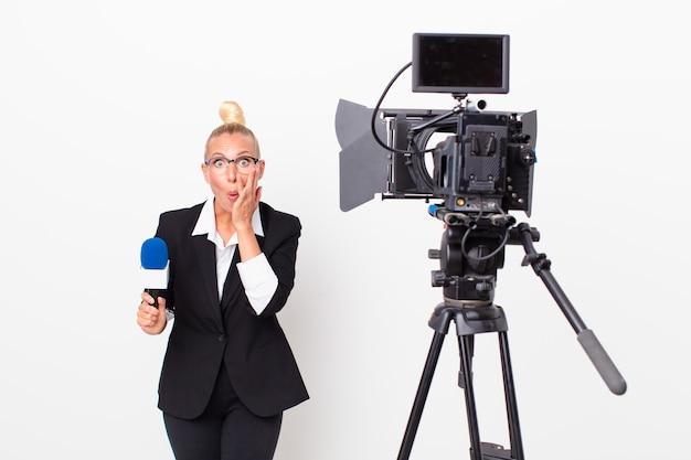 Довольно белокурая женщина чувствует себя потрясенной и напуганной и держит микрофон. концепция ведущего