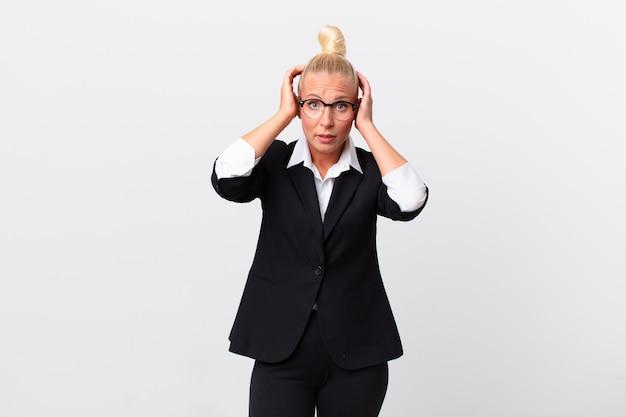 Довольно белокурая женщина чувствует стресс, тревогу или страх, с руками за голову. бизнес-концепция