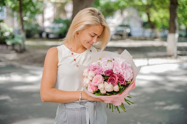 Pretty blond woman holding a beautiful composition of flowers