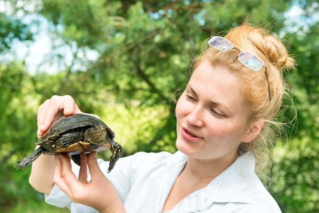 녹색 햇살이 비치는 배경 위에 애완용 거북이를 손에 들고 안경을 쓴 예쁜 금발 여성 프리미엄 사진