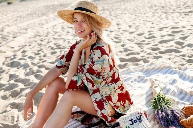 海の近くで休日を楽しんで、熱帯のビーチに座っている麦わら帽子のかなり金髪の女性。