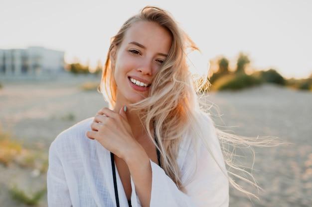 Довольно белокурая женщина в белой блузке позирует на пляже. летнее настроение. тропический отдых. волосы ветреные.
