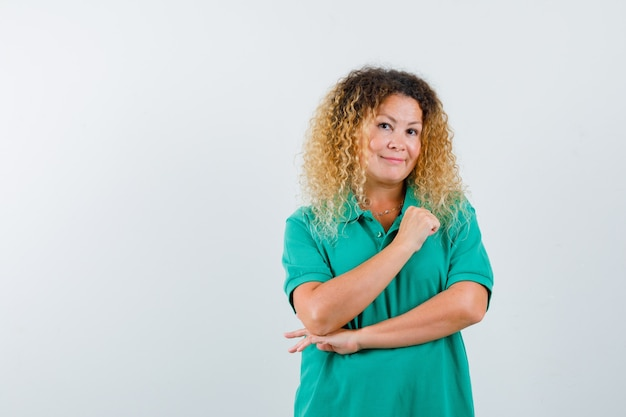 緑のポロtシャツで胸に腕を保ち、陽気に見えるかなり金髪の女性。正面図。