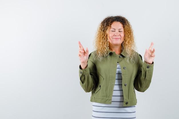 예쁜 금발 여자가 손가락을 엇갈리게 유지하고 녹색 재킷에 눈을 감고 평화로운 전면보기를보고 있습니다.