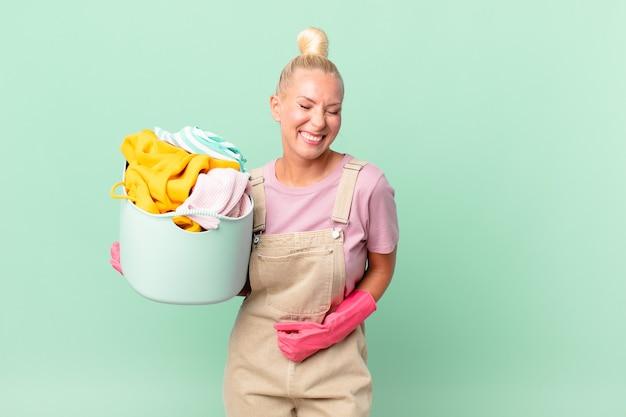 いくつかの陽気な冗談洗濯服の概念で大声で笑っているかなり金髪の女性