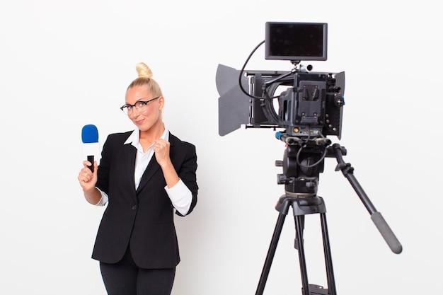 Довольно белокурая женщина, выглядящая высокомерной, успешной, позитивной и гордой, с микрофоном в руке. концепция ведущего