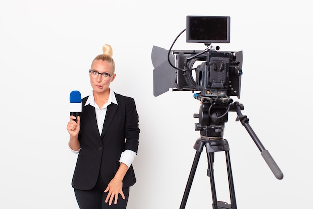 Pretty blond woman looking puzzled and confused and holding a pmicrophone. presenter concept