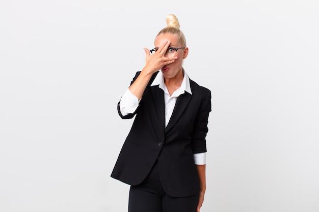 Довольно белокурая женщина выглядит потрясенной, напуганной или напуганной, закрывая лицо рукой. бизнес-концепция