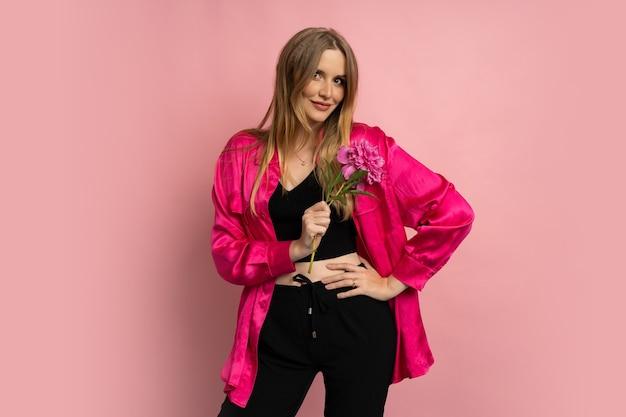 Довольно белокурая женщина позирует с цветком пиона в стильном летнем наряде над розовой стеной