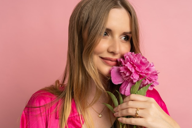 Pretty blond woman posing with peony flower in stylish summer outfit over pink wall