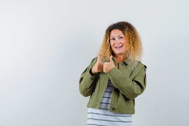 緑のジャケットで二重の親指を見せて、陽気に見えるかなり金髪の女性。正面図。