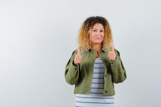 緑のジャケットで二重の親指を見せて、満足そうに見えるかなり金髪の女性、正面図。