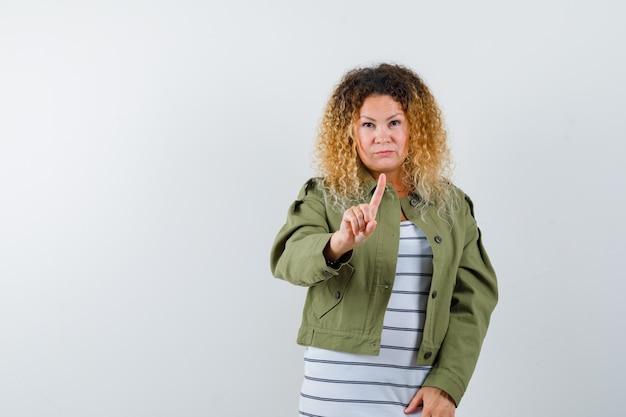 緑のジャケットで細かいジェスチャーを保持し、真剣に見える、かなり金髪の女性、正面図。