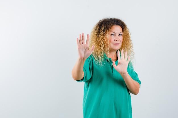 녹색 폴로 티셔츠에 자신을 방어하기 위해 손을 유지하고 무서워 보이는 예쁜 금발 여자. 전면보기.