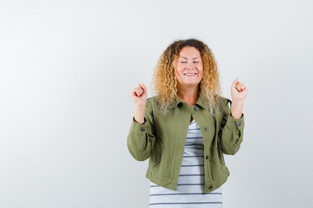 緑のジャケットで勝者のジェスチャーを示し、至福に見えるかなり金髪の女性。正面図。
