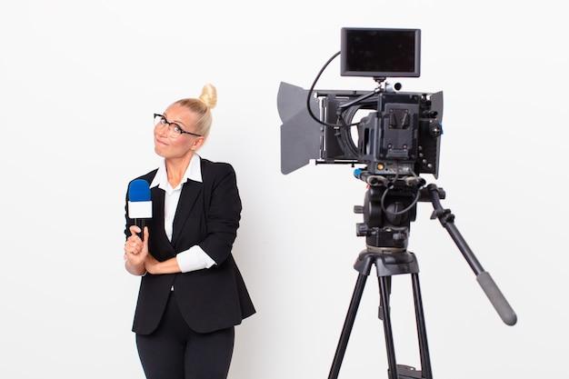 Довольно белокурая женщина пожимает плечами, чувствуя смущение и неуверенность, и держит микрофон в руках. концепция ведущего