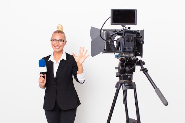 Довольно белокурая женщина улыбается и выглядит дружелюбно, показывает номер пять и держит микрофон. концепция ведущего