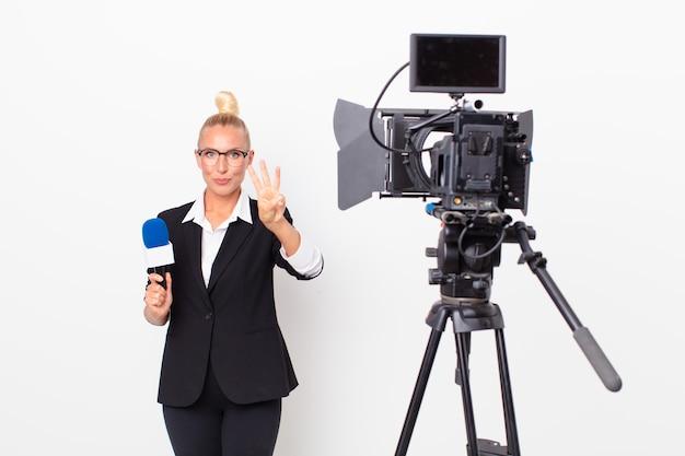 Довольно белокурая женщина улыбается и выглядит дружелюбно, показывает номер три и держит микрофон. концепция ведущего
