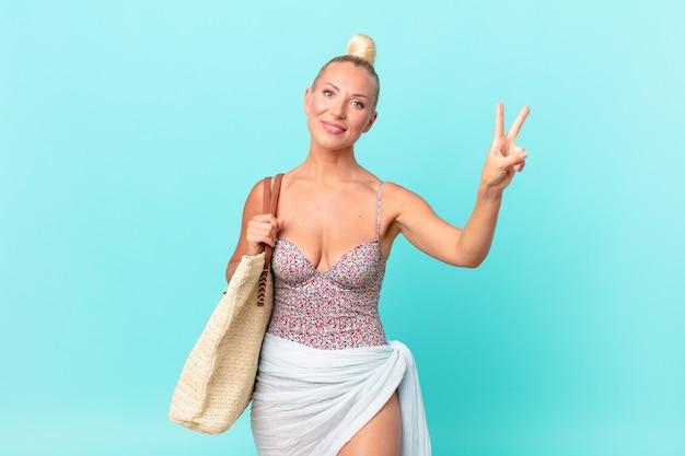 笑顔と幸せそうに見える、勝利または平和を身振りで示すかなり金髪の女性。夏のコンセプト