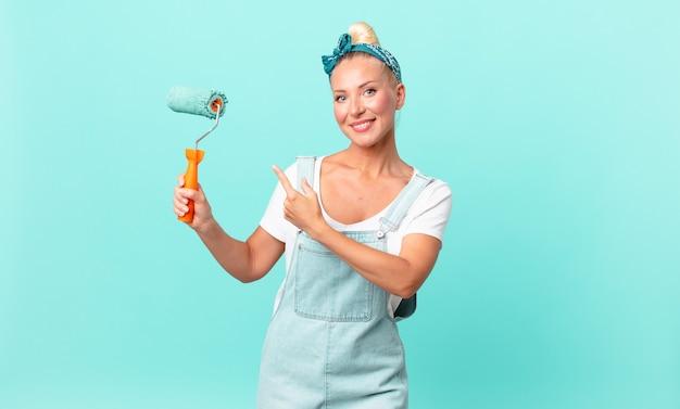 Довольно белокурая женщина весело улыбается, чувствует себя счастливой и указывает в сторону и красит стену
