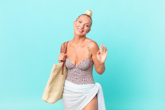 예쁜 금발 여성이 행복하게 웃고, 손을 흔들고, 환영하고 인사합니다. 여름 개념