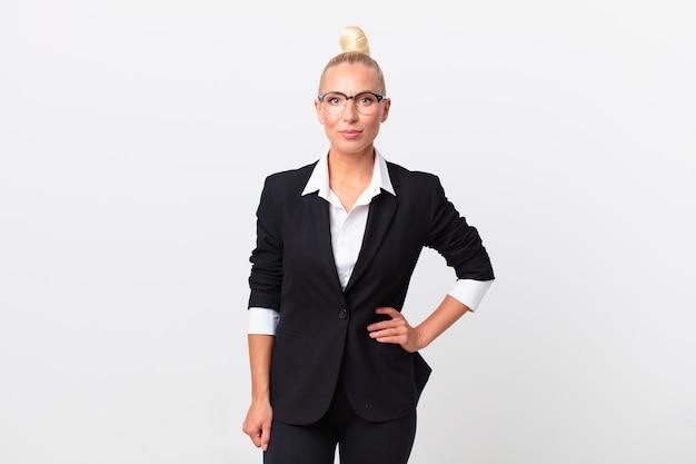 Довольно белокурая женщина счастливо улыбается, положив руку на бедро и уверенно. бизнес-концепция