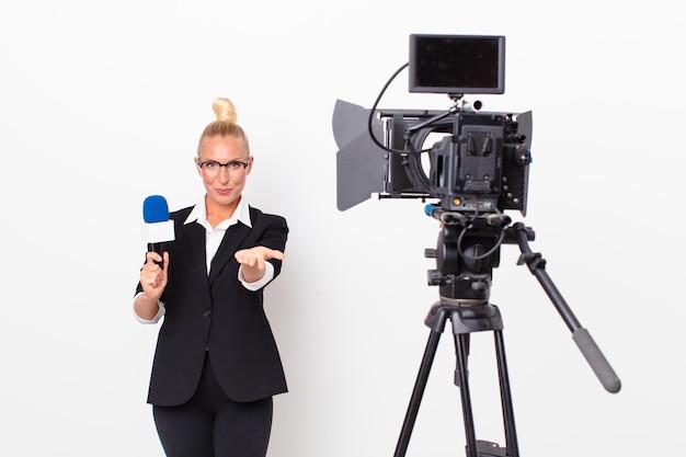 Довольно белокурая женщина счастливо улыбается с дружелюбными и предлагает и показывает концепцию и держит микрофон. концепция ведущего