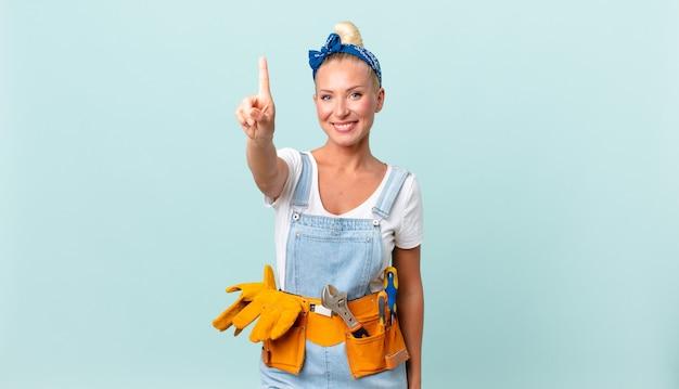 誇らしげにそして自信を持って笑顔でナンバーワンを作り、家のコンセプトを修復するかなり金髪の女性