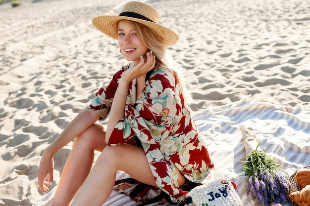 Donna abbastanza bionda in cappello di paglia che si siede sulla spiaggia tropicale, godendo le vacanze vicino all'oceano.