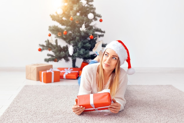 Довольно белокурая женщина в теплом вязаном свитере, лежа на ковре возле украшенной елки в гостиной. под елкой много подарков.