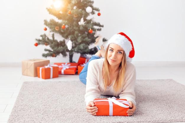 Довольно белокурая женщина в теплом вязаном свитере, лежа на ковре возле украшенной елки в гостиной. много подарков под деревом.