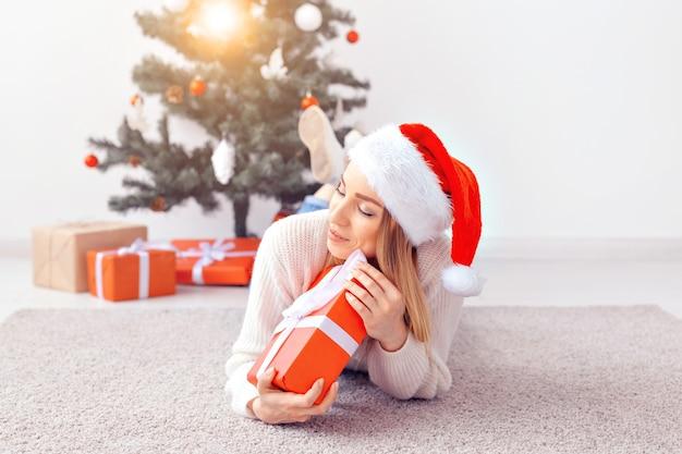 따뜻한 니트 스웨터를 입은 예쁜 금발 여성이 거실의 장식된 크리스마스 트리 근처 카펫에 누워 있습니다. 나무 아래 많은 선물.