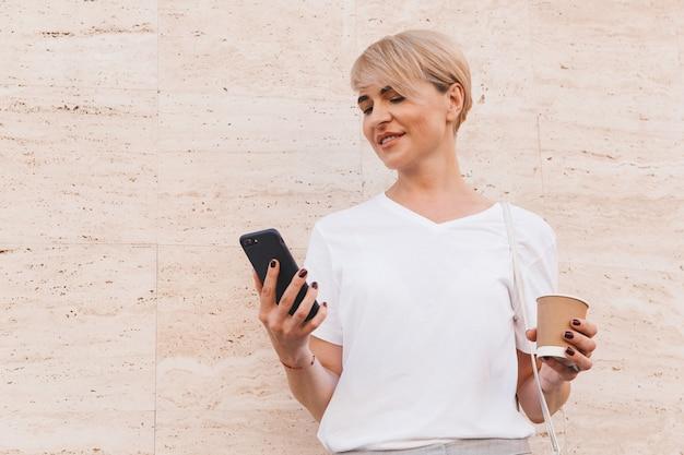 夏に屋外のベージュの壁に立って、紙コップからコーヒーを飲みながら、携帯電話を保持している白いtシャツを着ているかなり金髪の女性