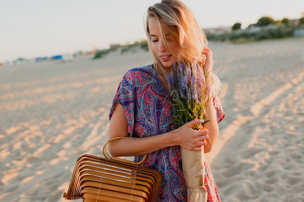 Довольно блондинка женщина с букетом лаванды, ходить на пляж. цвета заката.