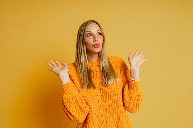 노란색에 포즈 오렌지 세련 된가 스웨터에 suprice 얼굴을 가진 예쁜 금발 여자.