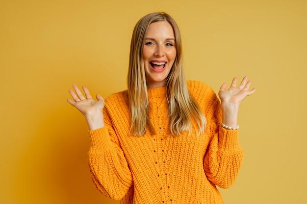Donna abbastanza bionda con la faccia di suprice in maglione autunnale alla moda arancione in posa sul giallo.