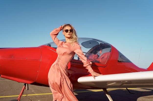 개인 비행기 근처에서 포즈를 취하는 핑크 실크 고급 드레스를 입고 물결 모양의 머리를 가진 예쁜 금발 여자